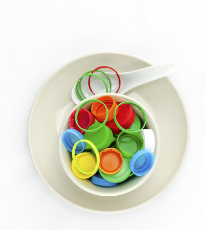 Recycle  plastic caps waste in bowl and plate with spoon isolated on white background photo