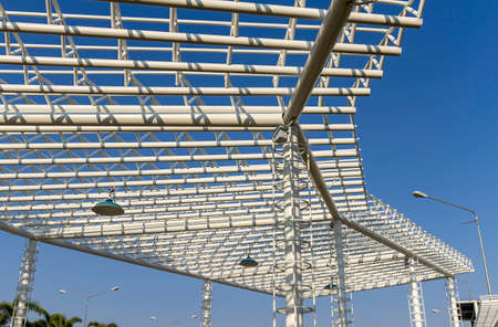 Architecture of metal structure texture with electric lamp against on blue sky photo