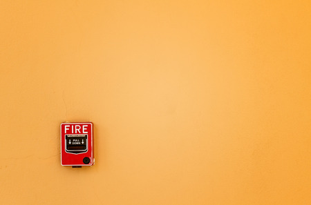 Red box of fire break glass on yellow wall background photo