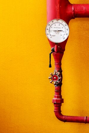 Water pressure gauge of the fire extinguisher with red water pipe on wall photo