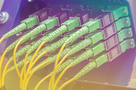 Server with set of green fiber optic cables in data center photo