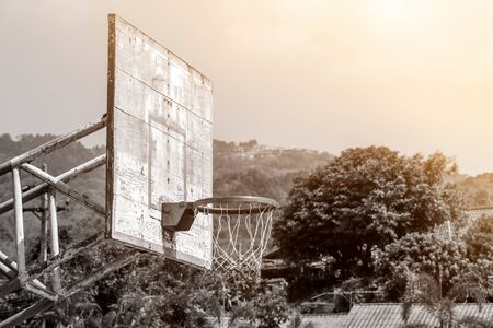 iron hoops: Black and white of old outdoor basketball backboard with hoop and net in countryside school Stock Photo