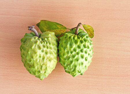 annonaceae: Fresh Custard apple tropical fruit on brown wood background Stock Photo