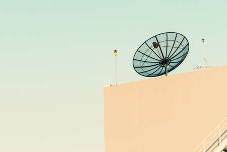 high frequency: Satellite dish antenna mounted on rooftop in urban area on blue sky