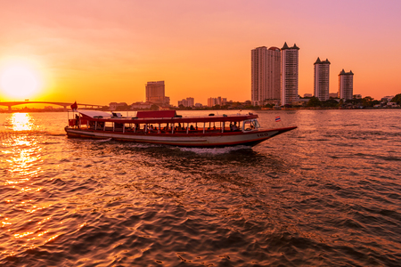 Dramatic sunset on river with building and boat in Chaophraya river, Bangkok, Thailand Stock Photo