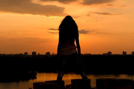 mujer desnuda sentada: Silueta de la muchacha en la hermosa puesta de sol permanecer en la parte superior del mirador Foto de archivo