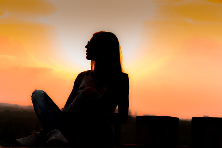 Silhouette of girl on beautiful sunset sitting on the top of the belvedere photo
