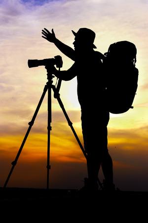 Photographers silhouette with camera on tripod on beautiful sunset photo