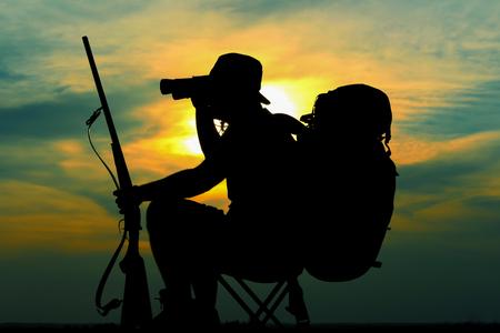 Hunters silhouette with hunting rifle watching through binoculars on beautiful sunset photo