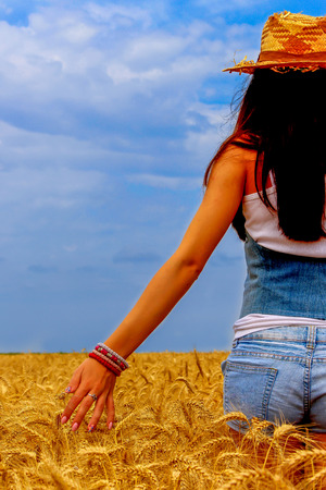 body scape: Beautiful woman in rye field on the blue sky