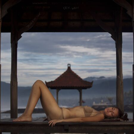 Young woman in swimwear resting at the beach inside the bower during sunrise photo