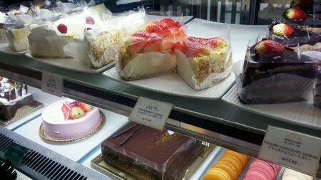 Display of various cakes and desserts at a store