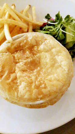 Chicken and mushroom pie with fries and salad on the side Stock Photo