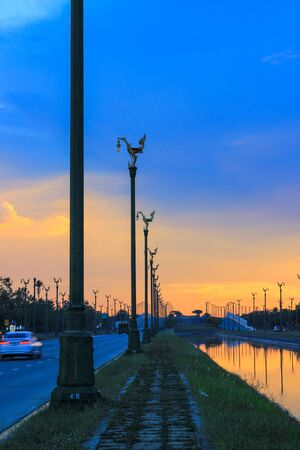 twilight sky at Thanon Utthayan(Aksa Road),Bangkok,Thailand-one of the most beautiful roads in Thailand.Along both sides of the road are 979 lamp posts decorated with the Thai phoenix Stock Photo