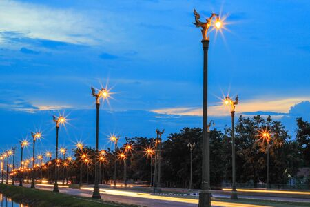 thanon: twilight sky at Thanon Utthayan(Aksa Road),Bangkok,Thailand-one of the most beautiful roads in Thailand.Along both sides of the road are 979 lamp posts decorated with the Thai phoenix Stock Photo