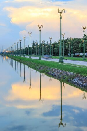 thanon: Evening sky at Thanon Utthayan(Aksa Road), Bangkok, Thailand-one of the most beautiful roads in Thailand. Along both sides of the road are 979 lamp posts decorated with the Thai phoenix Stock Photo