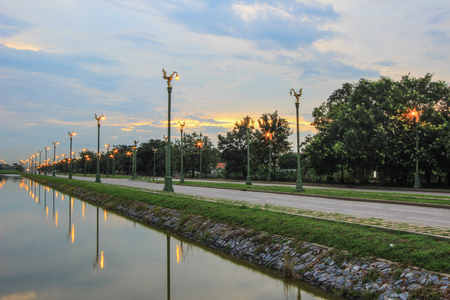thanon: Evening sky at Thanon Utthayan (Aksa Road), Bangkok, Thailand-one of the most beautiful roads in Thailand. Along both sides of the road are 979 lamp posts decorated with the Thai phoenix