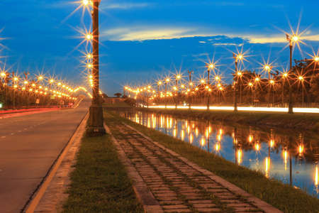 thanon: twilight sky at Thanon Utthayan (Aksa Road), Bangkok, Thailand-one of the most beautiful roads in Thailand. Along both sides of the road are 979 lamp posts decorated with the Thai phoenix Stock Photo