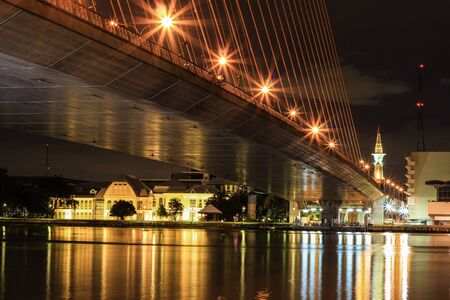 phrom: night view under the Rama VIII bridge in Bangkok, with Bang Khun Phrom Palace (now housing the museum of the Bank of Thailand) in the distance Stock Photo