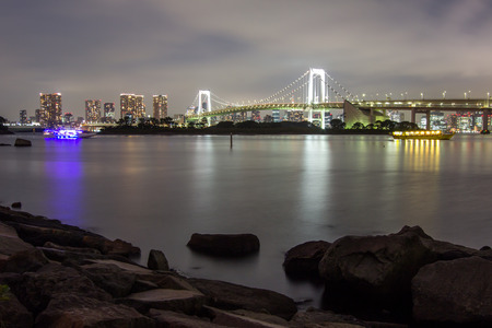 Night view of Rainbow Bridge and the surrounding Tokyo Bay area as seen from Odaiba,Minato, Tokyo, Japan.