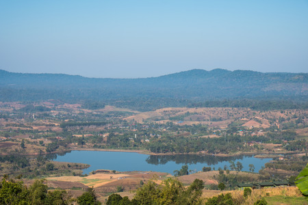 Thin fog,hills cascading beautifully and Rattanai reservoir as seen from the Viewpoint opposite to  district office of Khao Kho,Phetchabun Province,northern Thailand. Banco de Imagens - 86584678