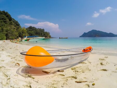 Kawthoung, Myanmar - April 6, 2018 : Transparent kayak for tourists on white sand beach of Flower Island