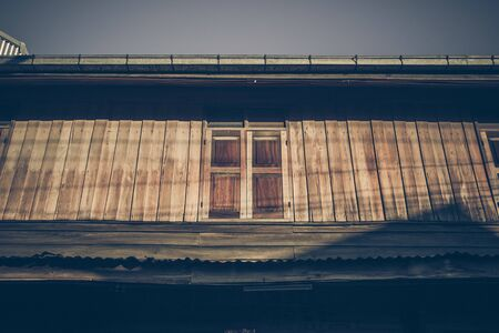 Old wooden houses along walking street(Chai Khong Road) in Chiang Khan,Loei,Thailand.Close-up the windows. Фото со стока