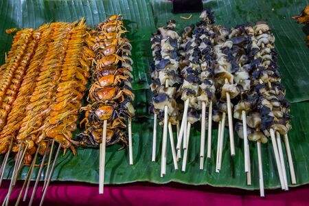 Street foods at walking street(Chai Khong Road) in Chiang Khan,Loei,Northeastern Thailand.-grilled shrimp skewers,grilled crab skewers,grilled shellfish skewers. Фото со стока