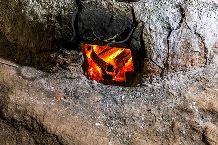 Burning firewood in the old stove for boiling salt water to make mountainous salt at Bo Kluea village,Nan Province,northern Thailand.(selective focus) Stok Fotoğraf