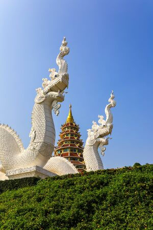 Wat Huay Pla Kang,Rimkok district,Chiang Rai Province,Northern Thailand:Beautiful white Naga staircases of the prayer hall,with 9 layers pagoda in the distance.(selective focus)