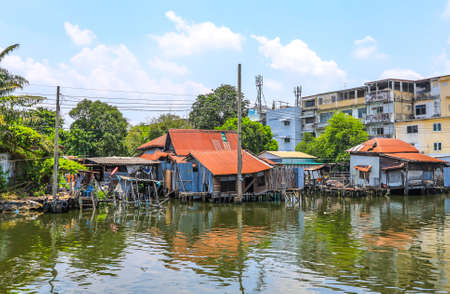 Bangkok,Thailand on May1,2020:Rural scene of old waterside houses along Khlong Bangkok Yai(Bangkok Yai Canal).