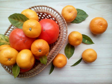 bright: Tangerines, persimmons in basket and green leaves on a bright wooden background