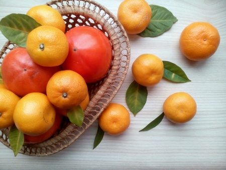 persimmons: Tangerines, persimmons in basket and green leaves on a bright wooden background