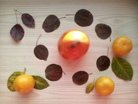 bright: Tangerines, persimmon and leaves on a bright wooden background Stock Photo