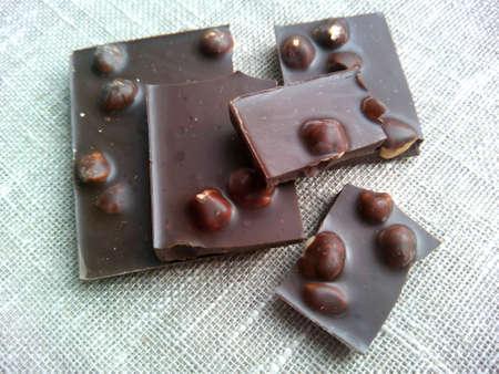 dark: Dark chocolate with hazelnuts on a natural background Stock Photo