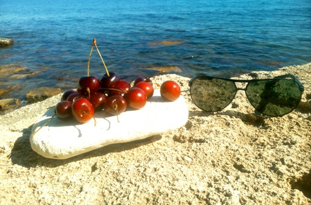 black white red: Red cherry and sunglasses on a sea stone rock background Stock Photo
