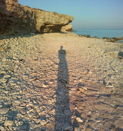 people shadow: Shadows girl on the sea white stones beach beautiful landscape Stock Photo