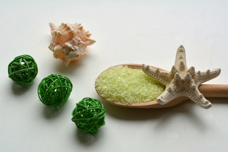 Spa green sea salt bath in wood spoon and shell