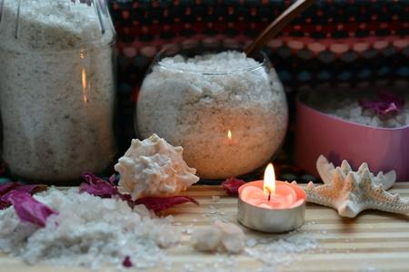 Spa sea salt bath and burning candle wood table background