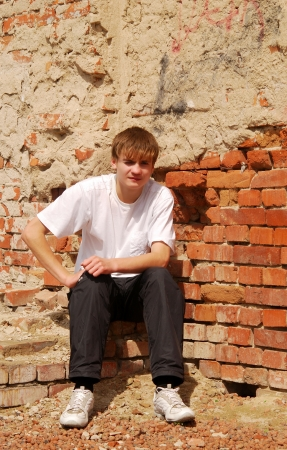young guy sits against a brick wall Stock Photo - 16324619