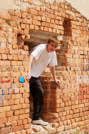 young guy sits against a brick wall Stock Photo - 16324621