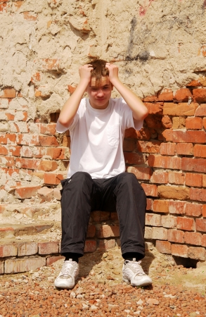 young guy in depression condition, sits against a brick wall Stock Photo - 16324616