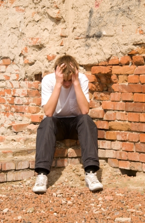young guy in depression condition, sits against a brick wall Stock Photo - 16324612