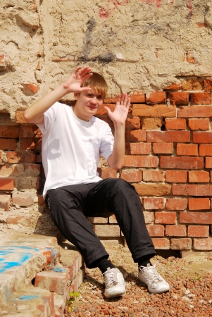 young guy sits against a brick wall Stock Photo - 16324623