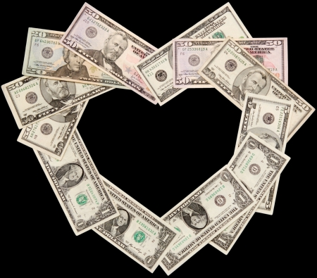 Heart is laid out from dollars of various face value, isolated on a black