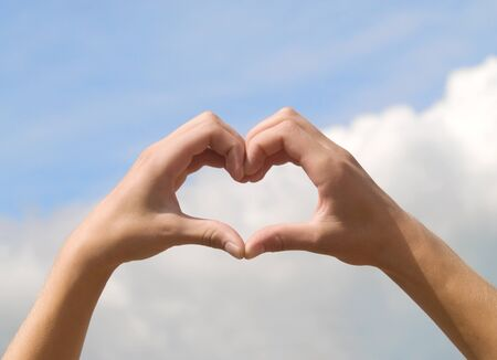hands in form of heart on blue sky background photo
