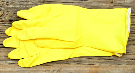 latex gloves: A pair of yellow latex gloves palms up single top folded edge on wooden background.