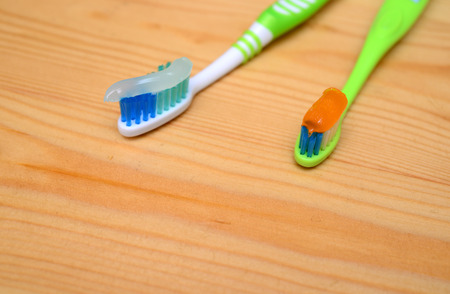 toothbrush with toothpaste on a wooden background