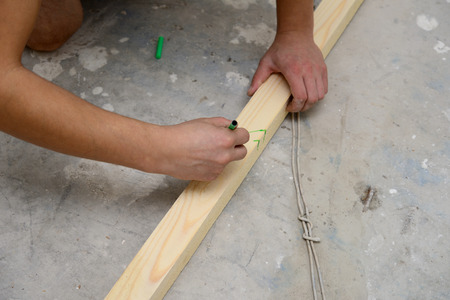 carpenter making marks on a wooden beam Stock Photo