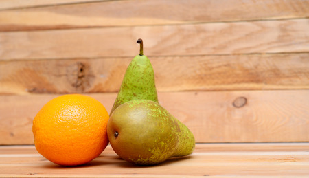 pears and oranges on the wooden background
